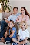 Happy young family sitting in the living room Stock Photo - Royalty-Free, Artist: 4774344sean                   , Code: 400-05751507