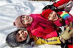 Happy friends in winterwear looking at camera while lying in snow Stock Photo - Royalty-Free, Artist: pressmaster                   , Code: 400-05753650