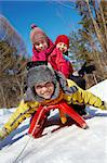 Happy friends in winterwear looking at camera while tobogganing Stock Photo - Royalty-Free, Artist: pressmaster                   , Code: 400-05753651
