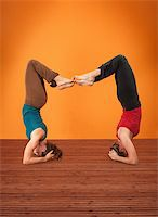 feet gymnast - Two women perform Vrisikasana yoga posture on a wooden mat Stock Photo - Royalty-Freenull, Code: 400-05754645