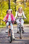 Mother and daughter on bicycle in autumn park