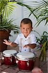 Hispanic baby boy playing bongos Stock Photo - Premium Royalty-Free, Artist: Ed Gifford, Code: 6106-05759283
