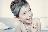 sucking - Little boy eating lollipop, portrait Stock Photo - Premium Royalty-Freenull, Code: 632-05760093