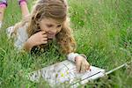 Girl lying in grass, using laptop computer Stock Photo - Premium Royalty-Free, Artist: Uwe Umsttter, Code: 632-05760321