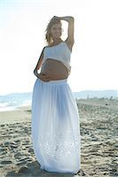 pregnant low angle - Pregnant woman standing on beach with hand on belly Stock Photo - Premium Royalty-Freenull, Code: 632-05760471