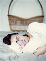 Mother and new born baby sleeping in bed Stock Photo - Premium Royalty-Freenull, Code: 632-05760583