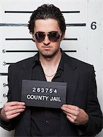 Studio mugshot of young man wearing sunglasses Stock Photo - Premium Royalty-Freenull, Code: 640-05760907