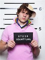 Mug shot of young man in baseball cap Stock Photo - Premium Royalty-Freenull, Code: 640-05760911