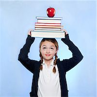 school girl uniforms - Studio shot of girl (10-11) holding stack of books and apple on head Stock Photo - Premium Royalty-Freenull, Code: 640-05761271