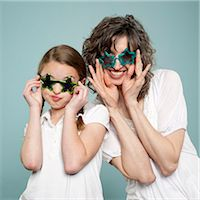 preteen touch - Studio shot of mother and daughter (10-11) wearing star shaped sunglasses Stock Photo - Premium Royalty-Freenull, Code: 640-05761279