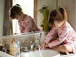 USA, Utah, Cedar Hills, Girl (4-5) sitting by bathroom sink, rinsing toothbrush Stock Photo - Premium Royalty-Free, Artist: Arcaid, Code: 640-05761316