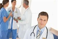 Portrait of young doctor with nurses and doctor in the background Stock Photo - Premium Royalty-Freenull, Code: 618-05761638