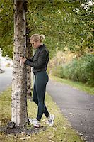 Jogger Stretching Calves Against Tree Stock Photo - Premium Rights-Managednull, Code: 700-05762106