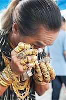 Man Wearing Lots of Jewelry Looking at Amulet Through Loupe Stock Photo - Premium Rights-Managednull, Code: 700-05762115