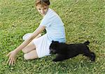 Girl sitting on grass, playing with puppy Stock Photo - Premium Royalty-Free, Artist: Kevin Dodge, Code: 695-05762538