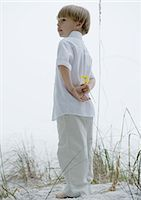 Little boy standing in dunes, holding flowers behind back Stock Photo - Premium Royalty-Freenull, Code: 695-05762835