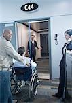 Man with traveler in wheelchair at boarding gate Stock Photo - Premium Royalty-Free, Artist: Michael Mahovlich, Code: 695-05763318