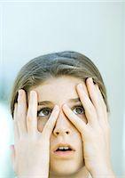 preteens fingering - Girl looking through fingers Stock Photo - Premium Royalty-Freenull, Code: 695-05763357