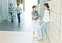 Two teen girls talking by lockers while boys run through hallway Stock Photo - Premium Royalty-Freenull, Code: 695-05763372