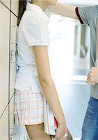 preteen girl boyfriends - Teen couple leaning against school lockers, mid section Stock Photo - Premium Royalty-Freenull, Code: 695-05763375