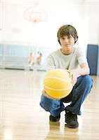 Teen boy crouching with basketball in school gym Stock Photo - Premium Royalty-Freenull, Code: 695-05763412