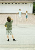Two girls playing in driveway while boy watches from street, hoolding ball Stock Photo - Premium Royalty-Freenull, Code: 695-05763533