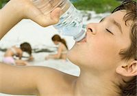 Boy drinking bottled water, girls playing in sand in background Stock Photo - Premium Royalty-Freenull, Code: 695-05763574