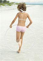 Girl running with plastic hoop on beach Stock Photo - Premium Royalty-Freenull, Code: 695-05763575