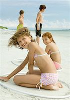 Girls sitting in rings, playing in sand on beach Stock Photo - Premium Royalty-Freenull, Code: 695-05763578