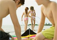 Boys preparing kite on beach, girls with hoola hoops in background Stock Photo - Premium Royalty-Freenull, Code: 695-05763579