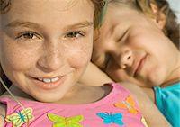 Girl in bathing suit, friend sleeping in background Stock Photo - Premium Royalty-Freenull, Code: 695-05763588