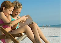 Girls reading book together on beach Stock Photo - Premium Royalty-Freenull, Code: 695-05763591