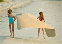 Two girls running on beach, holding blanket out in wind Stock Photo - Premium Royalty-Freenull, Code: 695-05763597