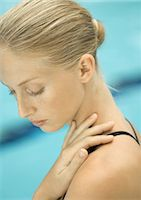 Woman with hand on shoulder, pool in background Stock Photo - Premium Royalty-Freenull, Code: 695-05763724