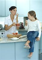 preteen thong - Girl sitting on kitchen counter while mother holds up container of tomato sauce Stock Photo - Premium Royalty-Freenull, Code: 695-05764214