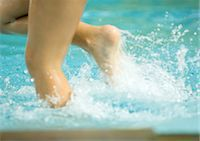 Child splashing in pool water, close-up of legs Stock Photo - Premium Royalty-Freenull, Code: 695-05764270