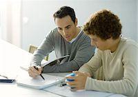 Man helping teenage son with homework Stock Photo - Premium Royalty-Freenull, Code: 695-05764313