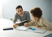 Father helping teenage son with homework Stock Photo - Premium Royalty-Freenull, Code: 695-05764332