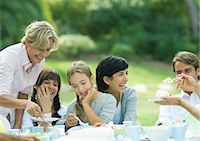 Outdoor birthday party, mature woman serving cake Stock Photo - Premium Royalty-Freenull, Code: 695-05764445