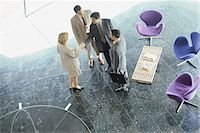 Businesswoman greeting businessmen in lobby, high angle view Stock Photo - Premium Royalty-Freenull, Code: 695-05764492