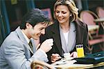 Businessman and woman sitting at sidewalk cafe Stock Photo - Premium Royalty-Free, Artist: Aurora Photos, Code: 695-05764545