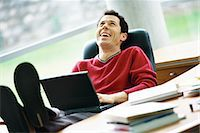 Man sitting at desk with feet up, holding laptop on lap, laughing Stock Photo - Premium Royalty-Freenull, Code: 695-05764746
