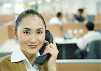 Businesswoman using phone in office Stock Photo - Premium Royalty-Freenull, Code: 695-05764943