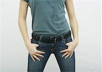 Young woman standing with thumbs in jean pockets, close-up of mid section Stock Photo - Premium Royalty-Freenull, Code: 695-05764964
