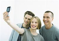 Three young friends taking photo together with cell phone Stock Photo - Premium Royalty-Freenull, Code: 695-05765106