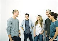 Group of young adult and teenage friends standing together, white background Stock Photo - Premium Royalty-Freenull, Code: 695-05765113