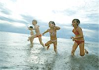 Four children racing in shallow water Stock Photo - Premium Royalty-Freenull, Code: 695-05765247