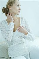 Woman sitting on bed, hand on neck, looking away Stock Photo - Premium Royalty-Freenull, Code: 695-05765487