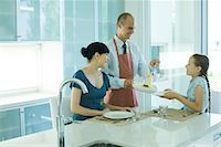 setting kitchen table - Man serving wife and daughter spaghetti Stock Photo - Premium Royalty-Freenull, Code: 695-05765642