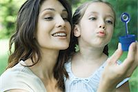 Girl and mother blowing bubbles together Stock Photo - Premium Royalty-Freenull, Code: 695-05765924